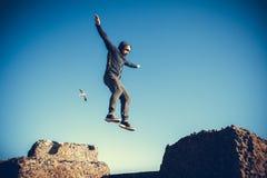 El hombre realiza salto freerunning en piedras Foto de archivo