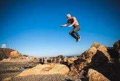 El hombre realiza salto freerunning en piedras Foto de archivo libre de regalías