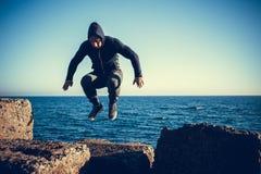 El hombre realiza salto freerunning en piedras Imagenes de archivo