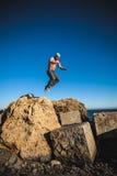 El hombre realiza salto freerunning en piedras Imagen de archivo libre de regalías