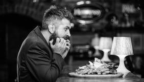 El hombre recibió la comida con los pescados fritos de la patata pega la carne Disfrute de la comida Alto bocado de la caloría Co imagenes de archivo