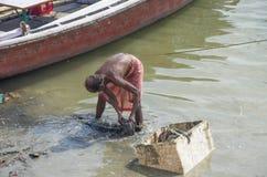 El hombre recoge la basura en el río la India de la cuadrilla Imagen de archivo libre de regalías