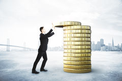 El hombre recoge una pila de monedas de oro, ahorrando concepto del dinero fotografía de archivo