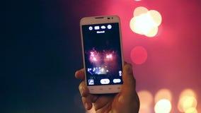 El hombre registra los fuegos artificiales video en el teléfono elegante almacen de video
