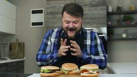 El hombre regordete satisfecho es feliz sobre las hamburguesas que él cocinó Sonrisa en la cara Forma de vida malsana, frita y ar almacen de metraje de vídeo
