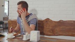 El hombre relajado está hablando por el teléfono que se sienta en café y que come el postre metrajes