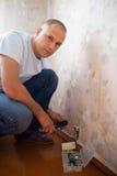 El hombre repara el socket Fotos de archivo libres de regalías