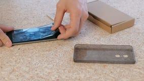El hombre repara el teléfono Remove agrietó el vidrio protector de la pantalla del ` s del teléfono