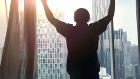 El hombre rico acertado joven admira el centro de ciudad con los rascacielos que la visión sube las manos durante puesta del sol  imagen de archivo