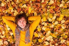 El hombre rizado en suéter amarillo y la bufanda mienten en las hojas de otoño Foto de archivo