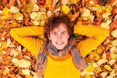 El hombre rizado en suéter amarillo y la bufanda mienten en las hojas de otoño fotografía de archivo