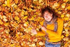 El hombre rizado en suéter y bufanda muestra algo en backgrond de las hojas Imagen de archivo