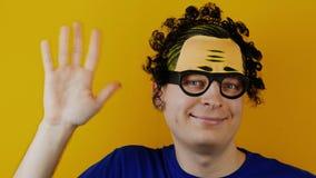 El hombre rizado graciosamente y cómico está agitando a mano almacen de metraje de vídeo