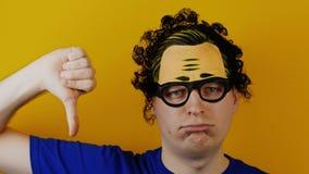 El hombre rizado graciosamente y cómico muestra el pulgar abajo o la aversión almacen de video