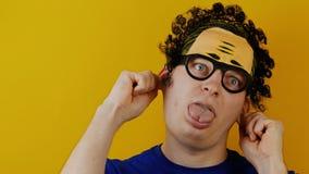 El hombre rizado insano se tira por los oídos y muestra su lengua, divertida alegre, las emociones humanas, en la pared amarilla almacen de video