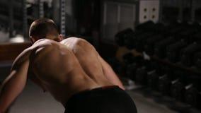 El hombre rodado con la ondulación muscles realizando los ejercicios para los hombros con pesas de gimnasia en el gimnasio almacen de metraje de vídeo