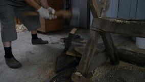 El hombre rompe a un tablero con un hacha almacen de metraje de vídeo