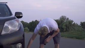 El hombre rubio está intentando fijar la compañía de automóviles quebrada de tres personas tiene amigos del accidente de tráfico  almacen de video