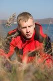 El hombre rubio joven en chaqueta roja se sienta en la costa. Fotografía de archivo