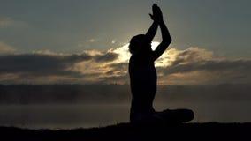 El hombre rubio se sienta en un banco del lago y practica yoga en la puesta del sol en la cámara lenta metrajes