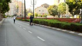 El hombre rueda el cochecito en la ciudad del coche-menos almacen de metraje de vídeo