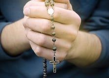 El hombre ruega con un rosario Fotos de archivo libres de regalías