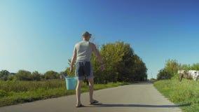 El hombre rural lleva un cubo de agua para regar almacen de video