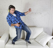 el hombre 20s o 30s saltó en el sofá que escuchaba la música en el teléfono móvil con los auriculares que jugaban Air Guitar Imágenes de archivo libres de regalías