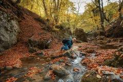 El hombre saca el agua de una corriente de la montaña foto de archivo libre de regalías