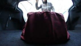 El hombre saca una maleta del tronco almacen de metraje de vídeo