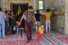 El hombre sale de la mezquita con el niño pequeño, Shiraz, Irán Imagen de archivo