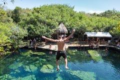 El hombre salta de un acantilado en el cenote de Cristalino en México fotografía de archivo libre de regalías