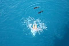 El hombre salta en el agua con salpica y las aletas Foto de archivo