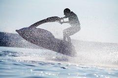 El hombre salta en el jetski Fotografía de archivo