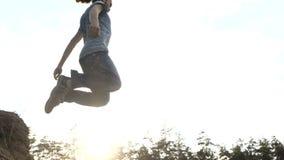 El hombre salta en una arena en la cámara lenta al aire libre en la puesta del sol metrajes