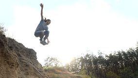 El hombre salta en una arena en la cámara lenta al aire libre en la puesta del sol almacen de metraje de vídeo