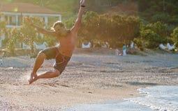El hombre salta en una playa Fotografía de archivo