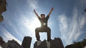 El hombre salta sobre fondo del cielo azul metrajes
