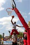 El hombre salta sobre Person To Perform Slam Dunk en competencia Foto de archivo