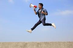 El hombre salta y grita megáfono Imagen de archivo
