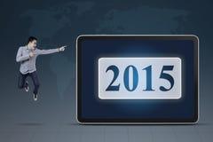 El hombre salta y señalando en el número 2015 Imágenes de archivo libres de regalías