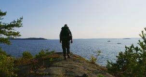 El hombre sano con la mochila grande camina en la montaña por el mar en la puesta del sol metrajes