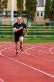 El hombre sano corre en pista del deporte de la raza del atletismo y c de la representación imagenes de archivo