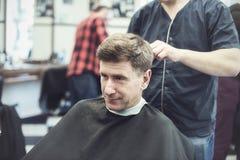 El hombre satisfecho, confiado en un salón de la peluquería disfruta del proc Imágenes de archivo libres de regalías
