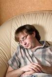 El hombre se cayó dormido en una silla Foto de archivo libre de regalías
