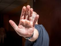 El hombre se cierra la cara con la mano El hombre quiere seguir siendo no identificado imagenes de archivo