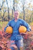 El hombre se coloca con dos calabazas enormes entre el leav colorido del otoño Fotografía de archivo libre de regalías
