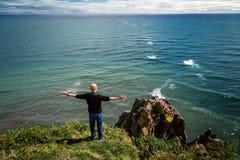 El hombre se coloca con los brazos abiertos en el acantilado delante del Océano Pacífico foto de archivo libre de regalías