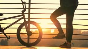 El hombre se coloca con una bici en un fondo de la puesta del sol, cierre para arriba almacen de metraje de vídeo