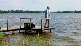 El hombre se coloca en el embarcadero en el lago en tiempo ventoso almacen de metraje de vídeo